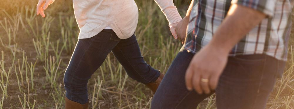 Couple holding hands in tall grass - family law